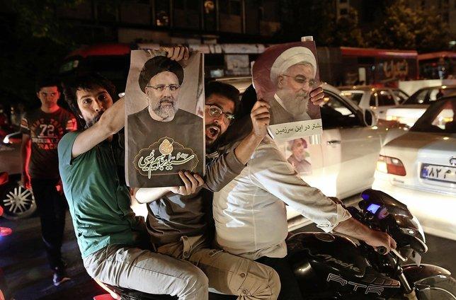 Etrange scène à Téhéran: sur la même moto, un partisan du président Hassan Rohani (sur l'affiche de droite) et un autre soutenant son rival Ebrahim Raisi (à gauche).  © Keystone